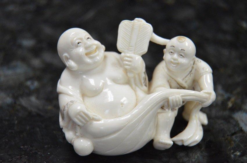IVORY NETSUKE OF BOY WITH BUDDAH