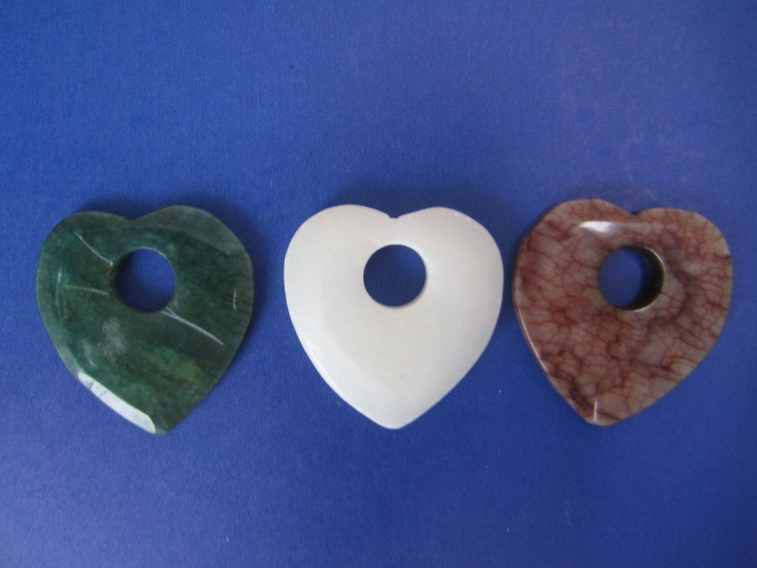 Three carved gemstone heart-shape plaques
