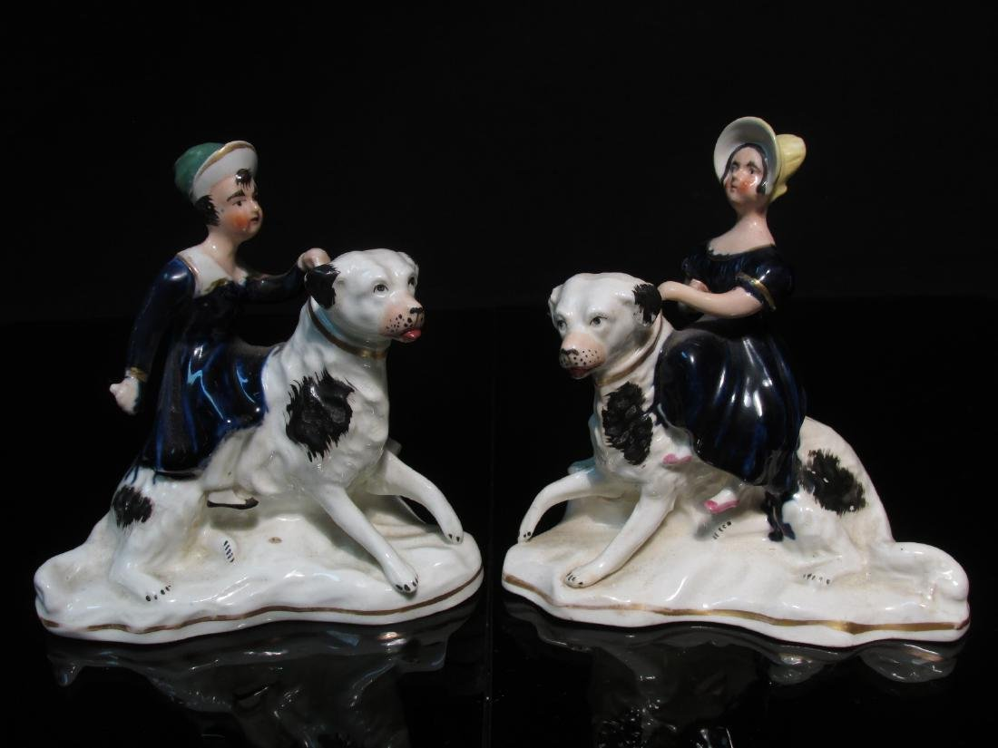 PAIR STAFFORDSHIRE ROYAL CHILDREN SEATED ON DOGS