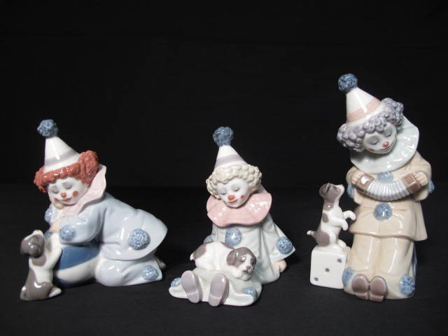 21: THREE LLADRO PORCELAIN CLOWNS WITH PUPPIES