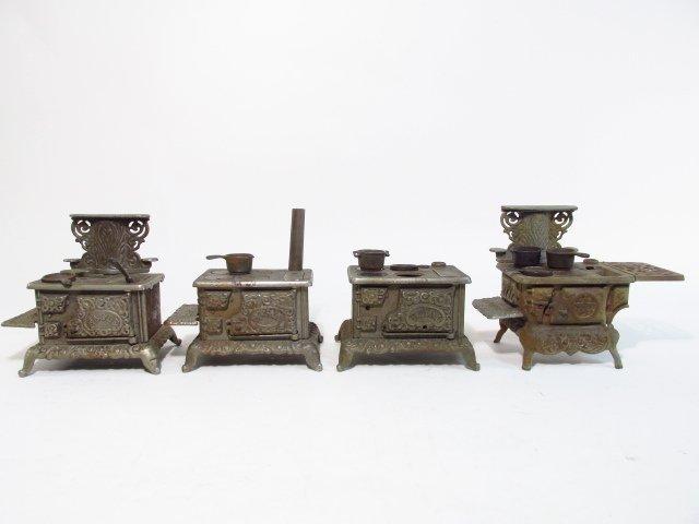 FOUR ANTIQUE DOLLHOUSE OR SALESMAN'S SAMPLE STOVES