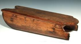 A 19TH CENTURY PRIMITIVE PINE CHILD'S SLED