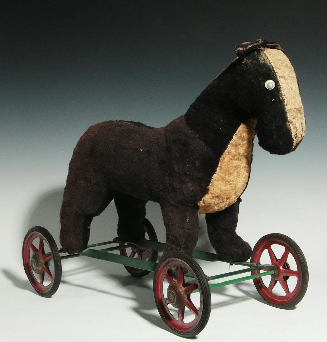 A VINTAGE PLUSH ANIMAL PULL TOY ON WHEELS