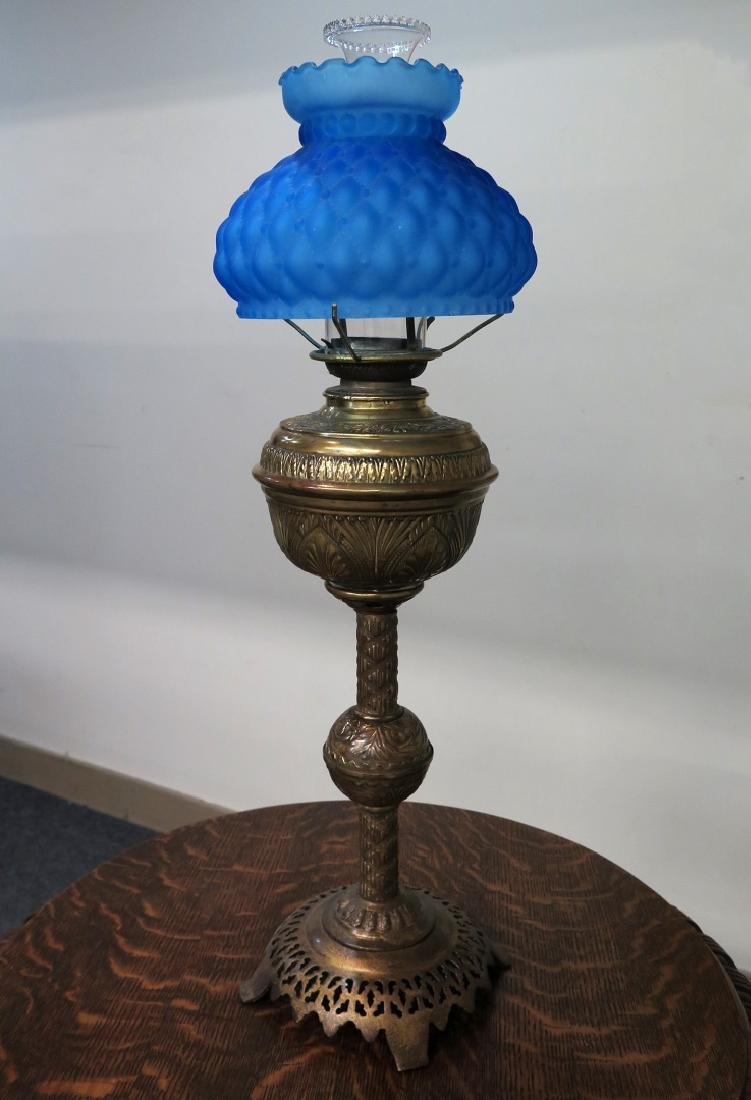 A 19TH C. BRASS OIL LAMP WITH BLUE QUILTED SHADE