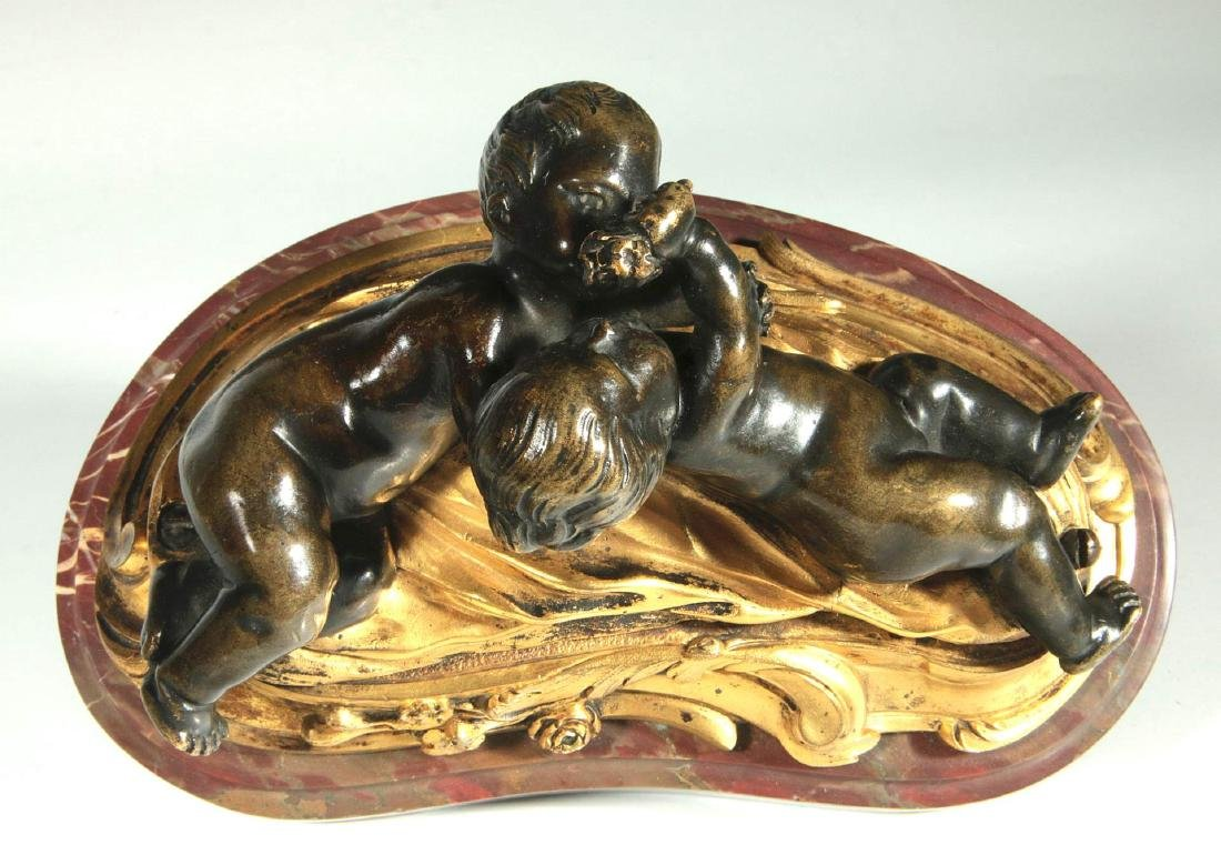 A GILT AND PATINATED BRONZE PUTTI GROUP