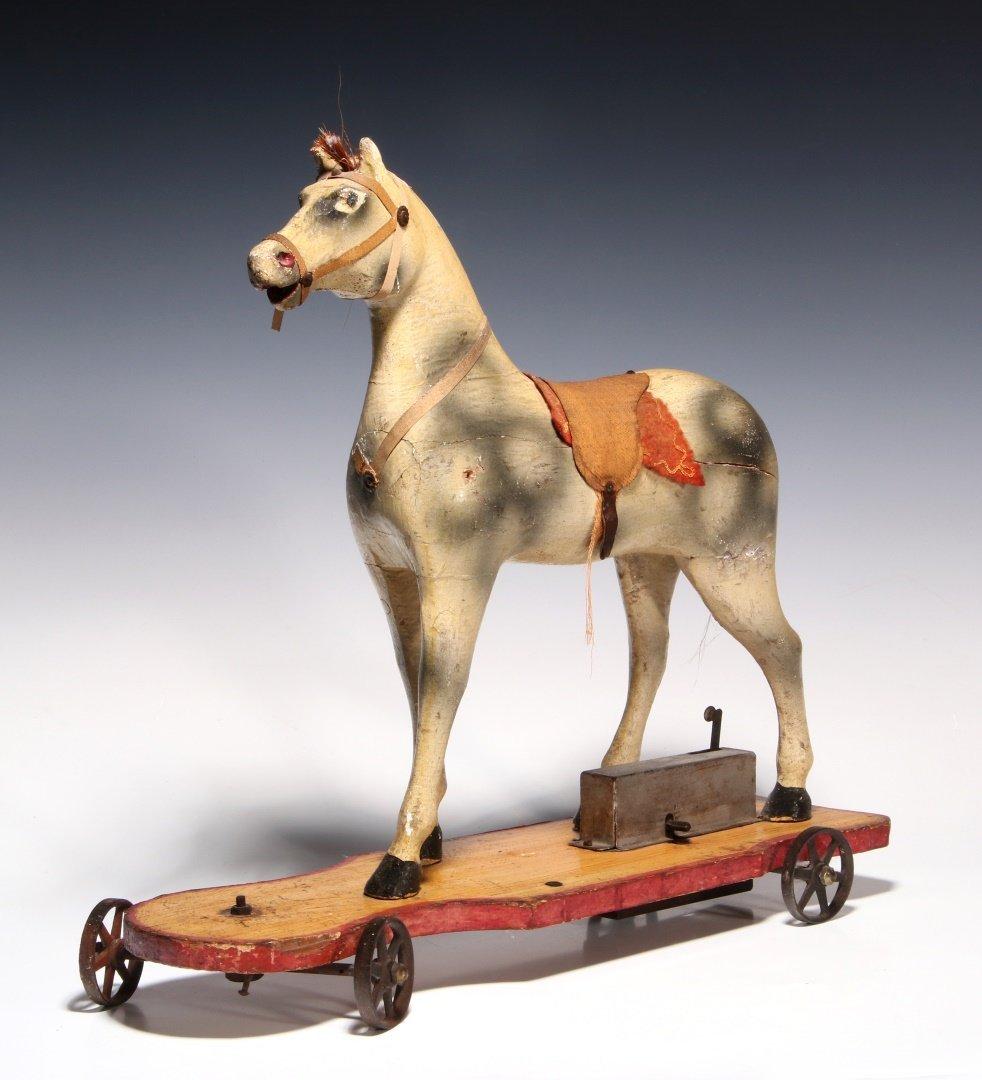 AN UNUSUAL 19TH C. KEY WIND PLATFORM HORSE ON WHEELS