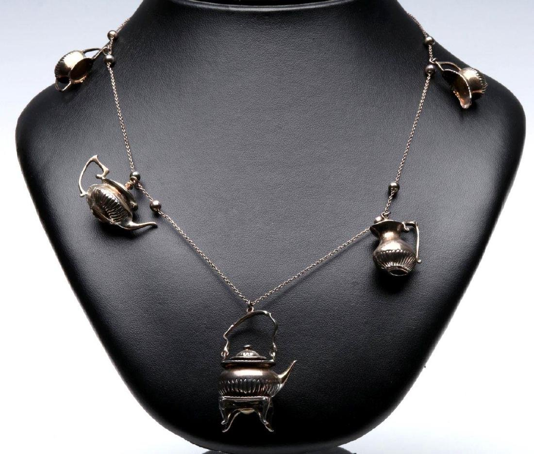 A STERLING SILVER NECKLACE WITH TEAPOT CHARMS