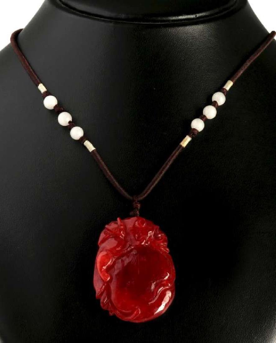 A CARVED RED JADE PENDANT