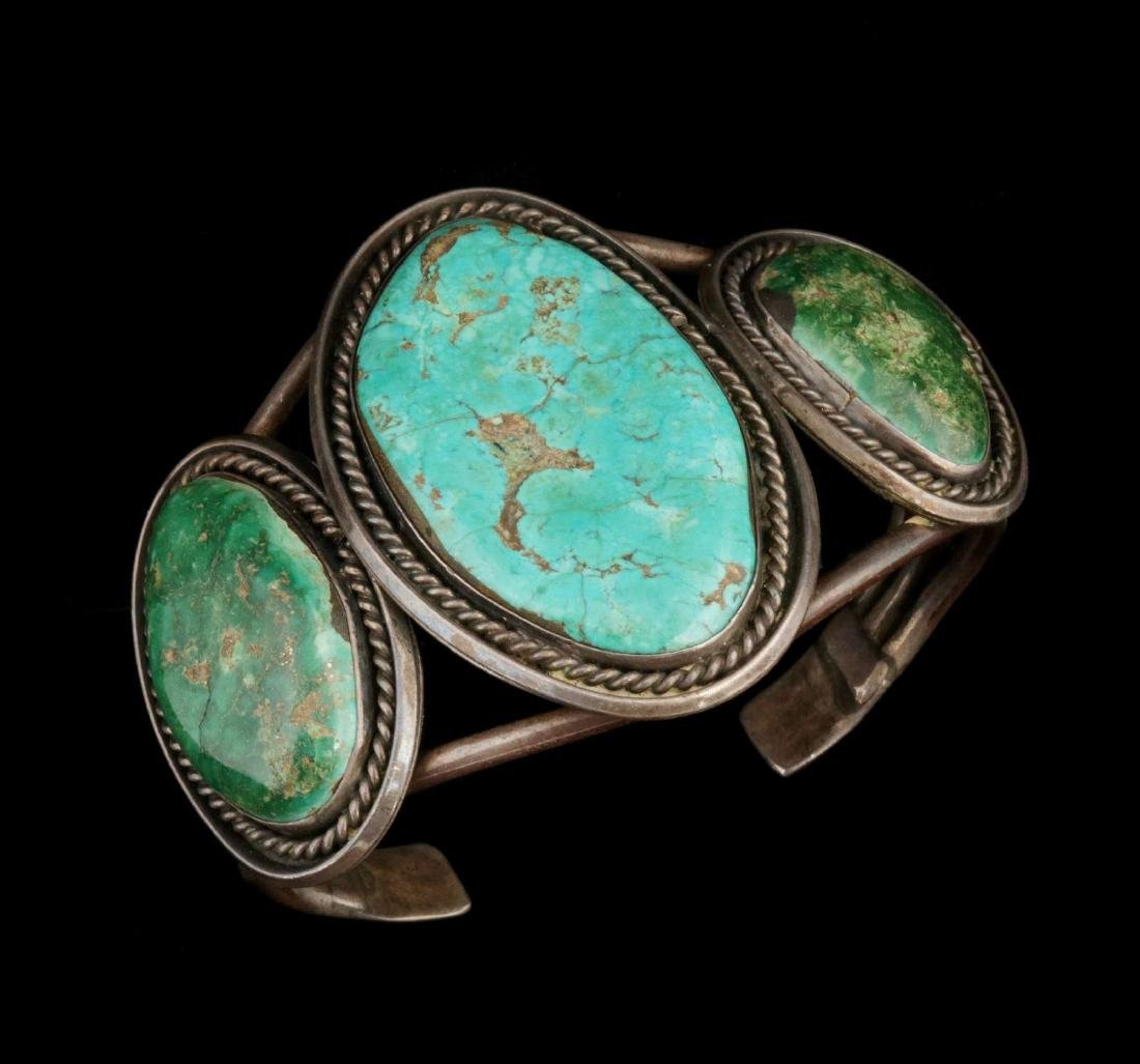 A LARGE STERLING AND TURQUOISE NAVAJO BRACELET