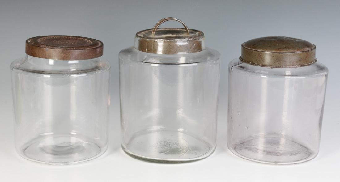 THREE EARLY BLOWN GLASS STORAGE JARS WITH TIN LIDS