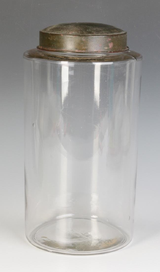 A TALL EARLY BLOWN GLASS STORAGE JAR WITH TOLE LID