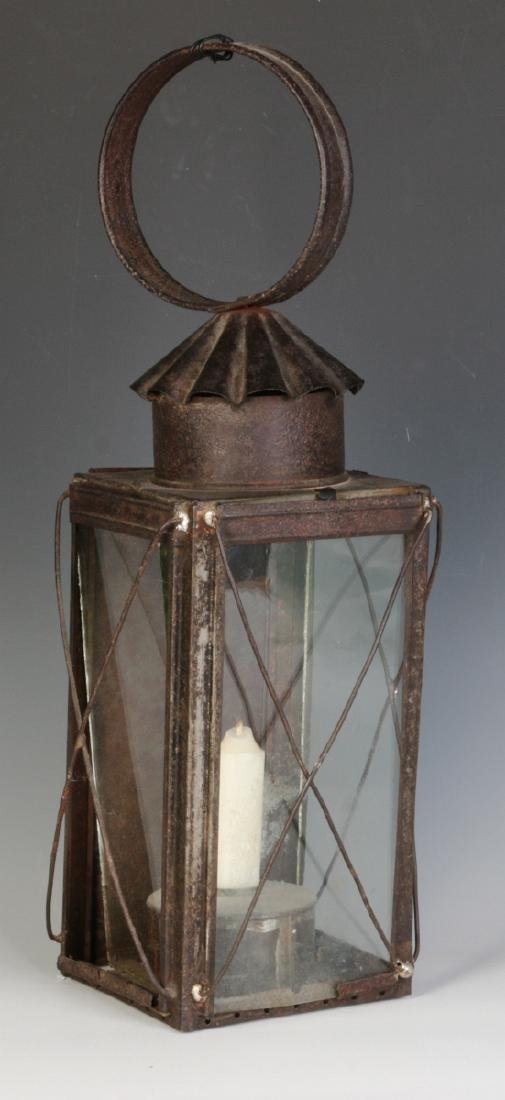 A 19TH CENTURY TIN AND GLASS CANDLE LANTERN