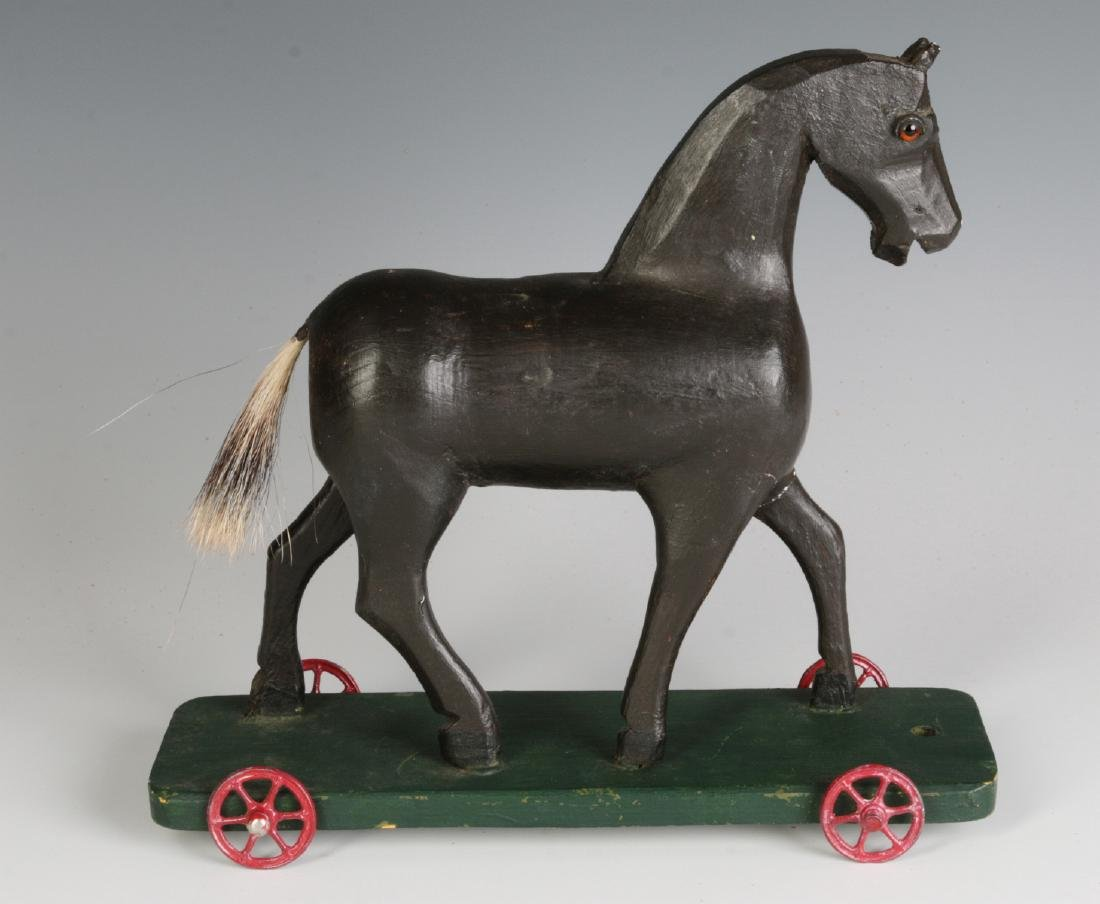 A CIRCA 1900 FOLK ART CARVED WOOD PLATFORM HORSE