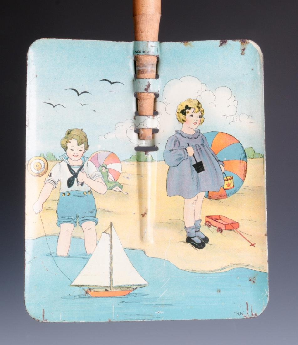 A TIN LITHO CHILD'S SAND SHOVEL WITH WOOD HANDLE