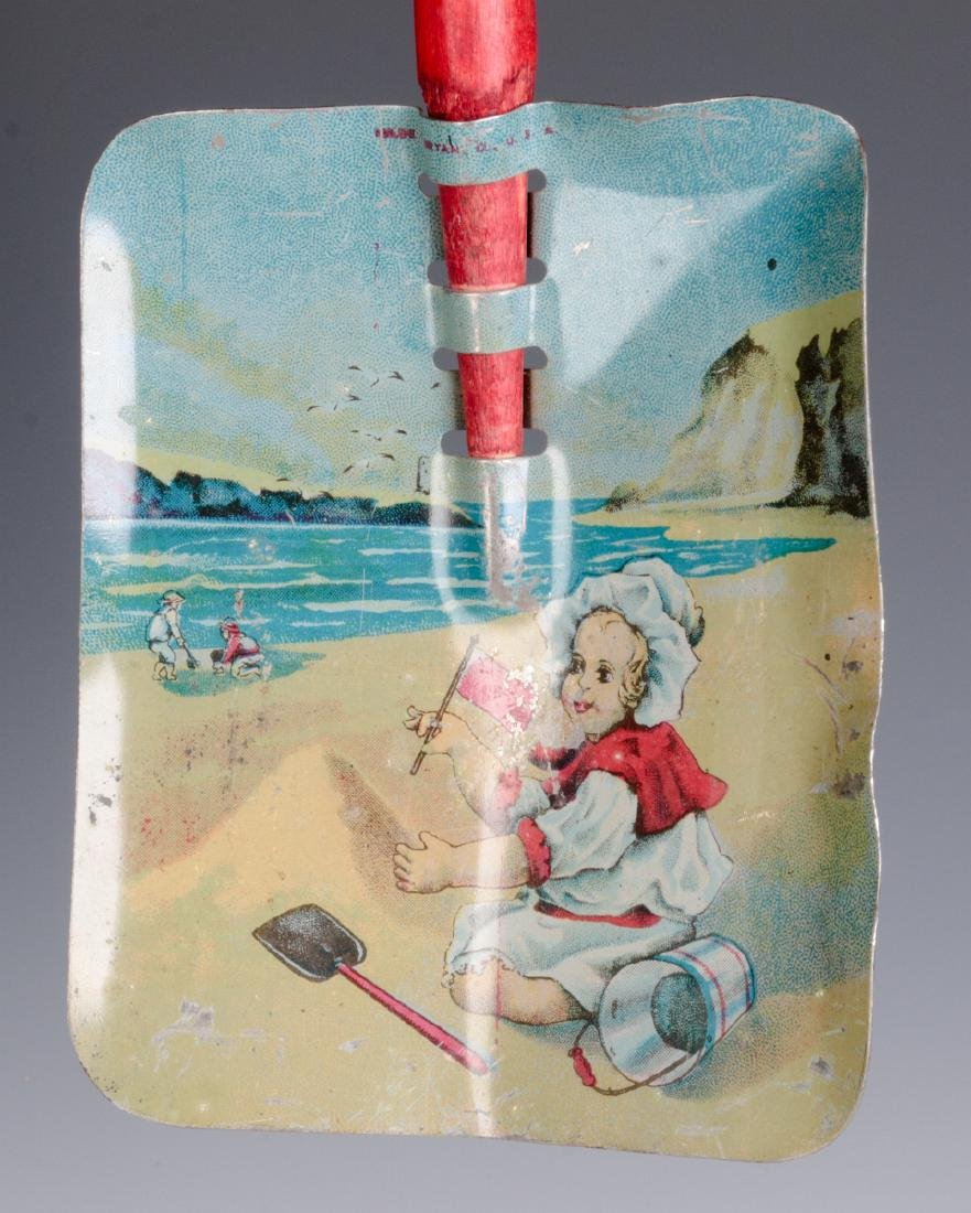 A CHILD'S TIN LITHO SAND SHOVEL WITH WOOD HANDLE