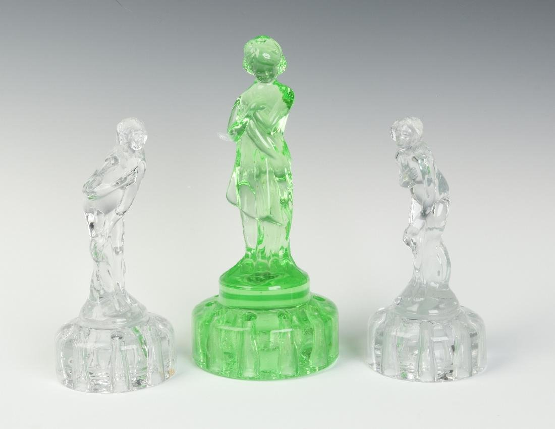 THREE CAMBRIDGE GLASS FIGURAL FLOWER FROGS