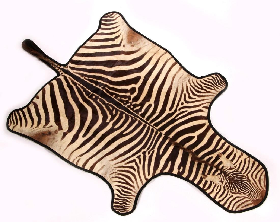 A TAXIDERMY AFRICAN ZEBRA HIDE RUG WITH FELT