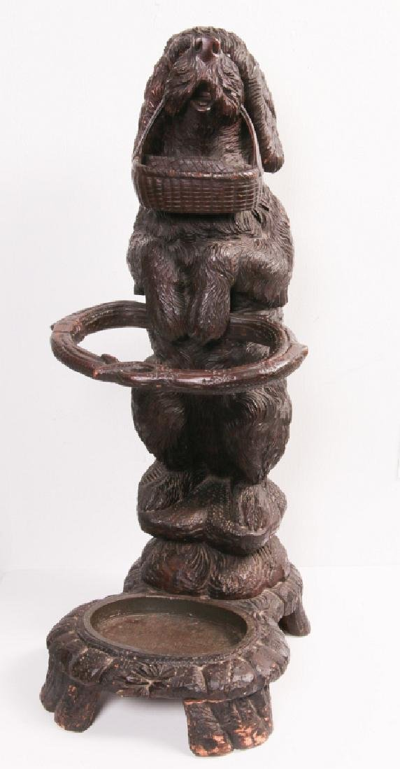 AN EARLY 20TH C BLACK FOREST CARVED DOG CANE STAND