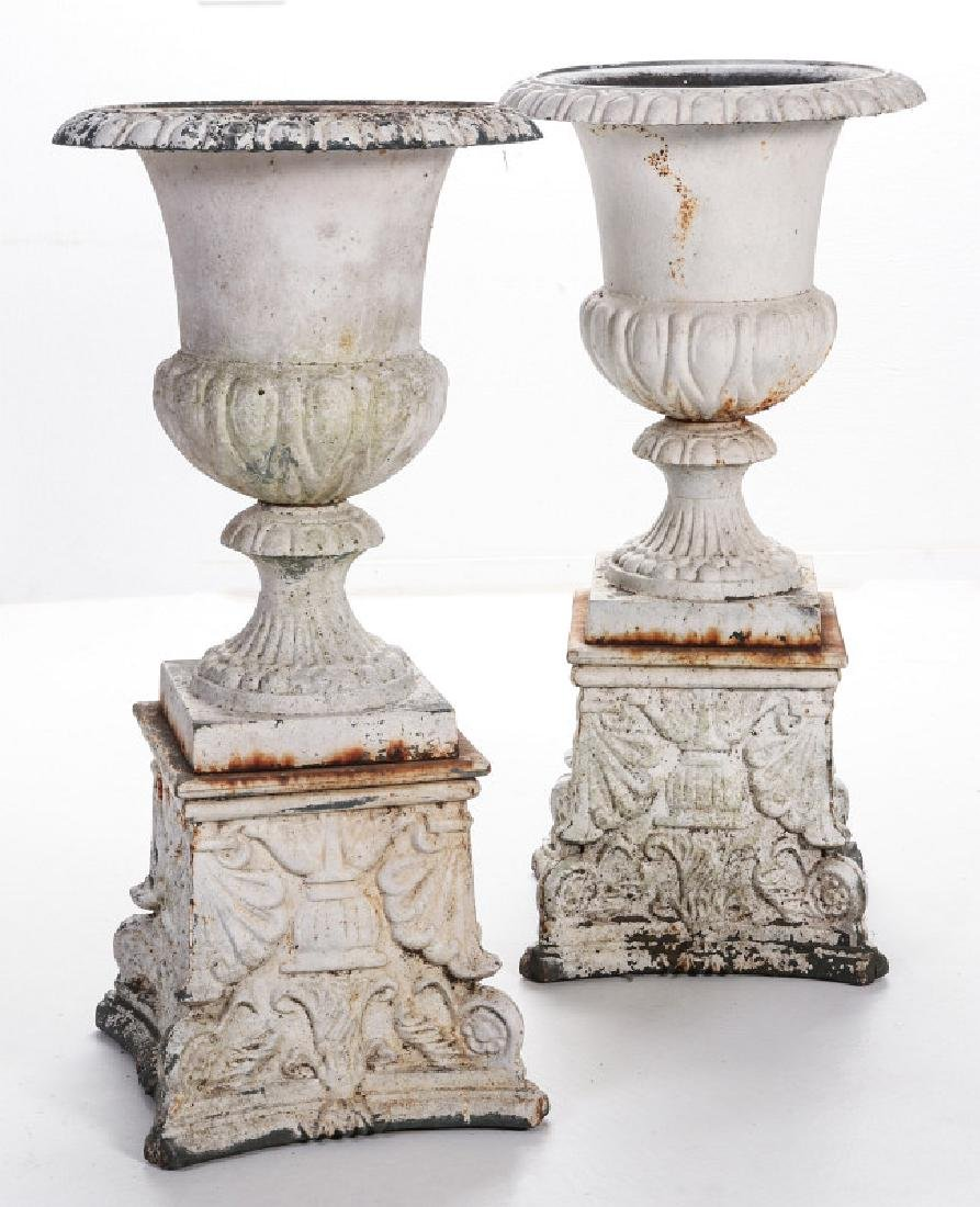 A PAIR OF CAMPAGNA FORM CAST IRON URNS ON PLINTHS