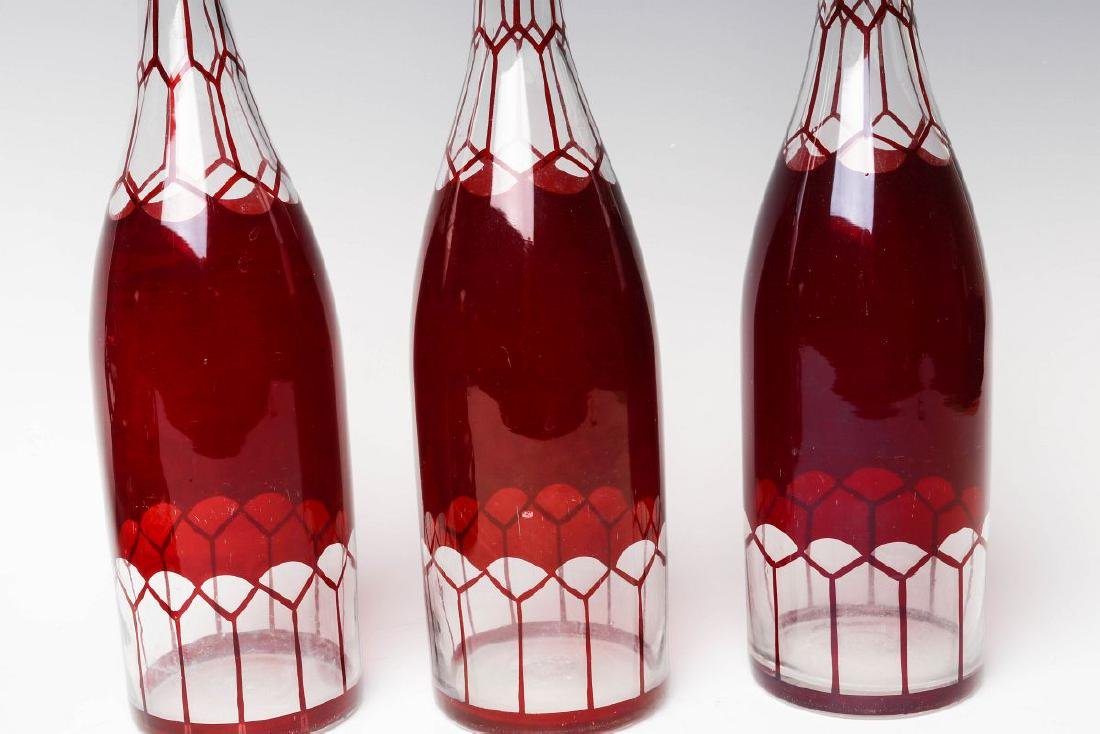 THREE RUBY FLASH WINE DECANTERS IN STAND - 10