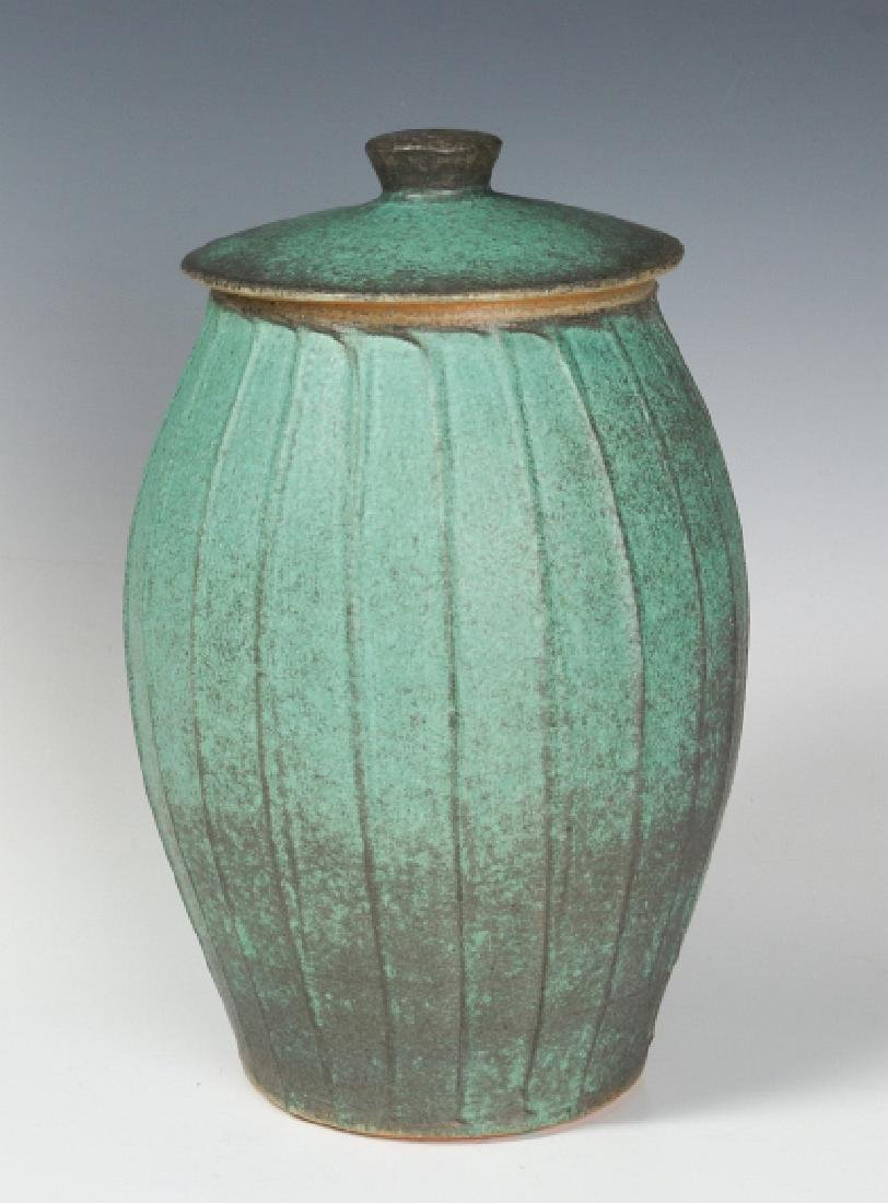 A COVERED STONEWARE JAR SIGNED LOWE 2000