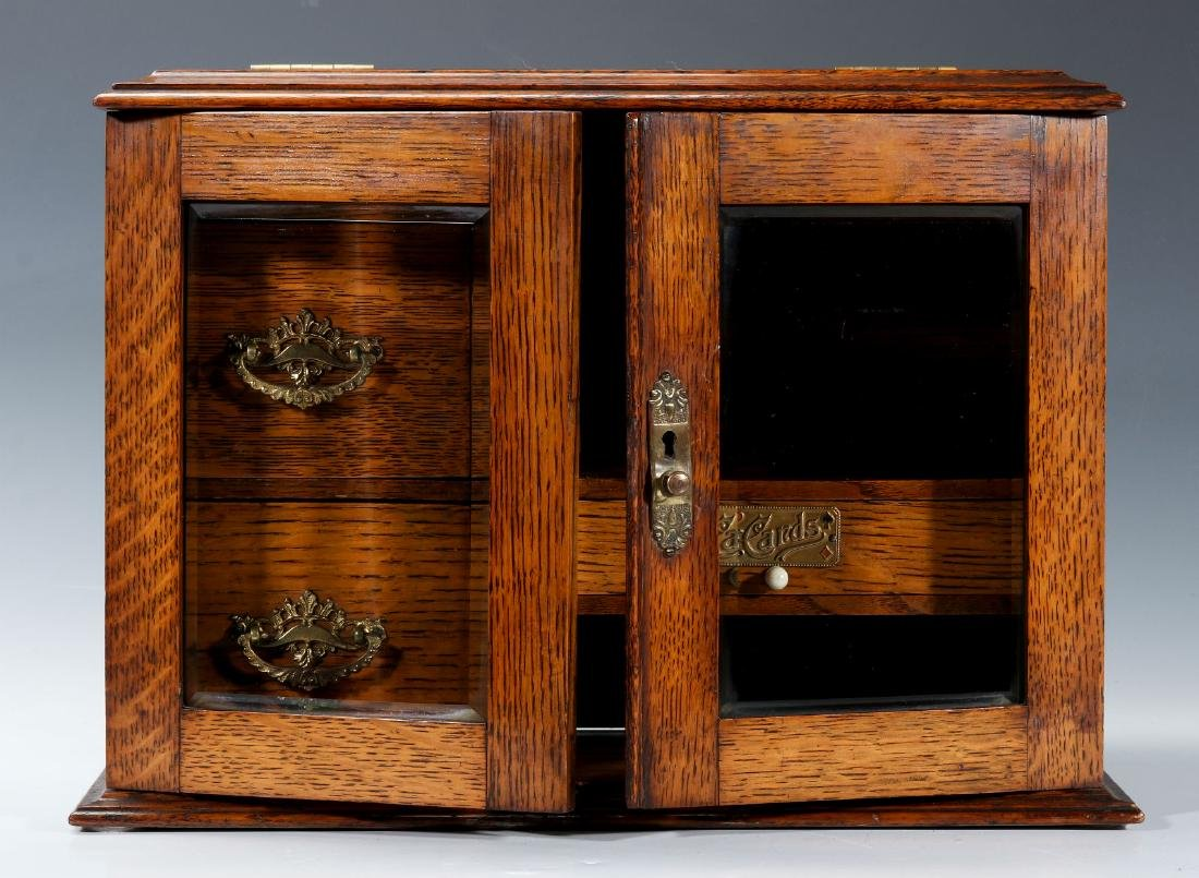 A CIRCA 1920s OAK PLAYING CARD AND GAMES CABINET