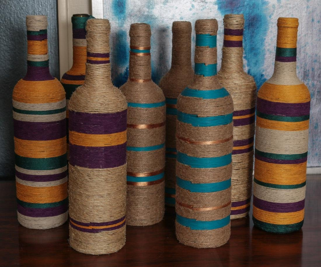 A COLLECTION OF COLORFUL TWINE WRAPPED BOTTLES
