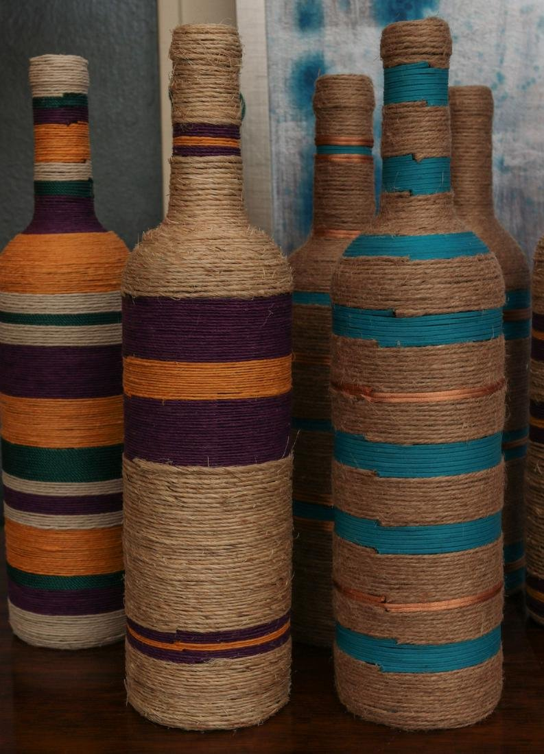 A COLLECTION OF COLORFUL TWINE WRAPPED BOTTLES - 2