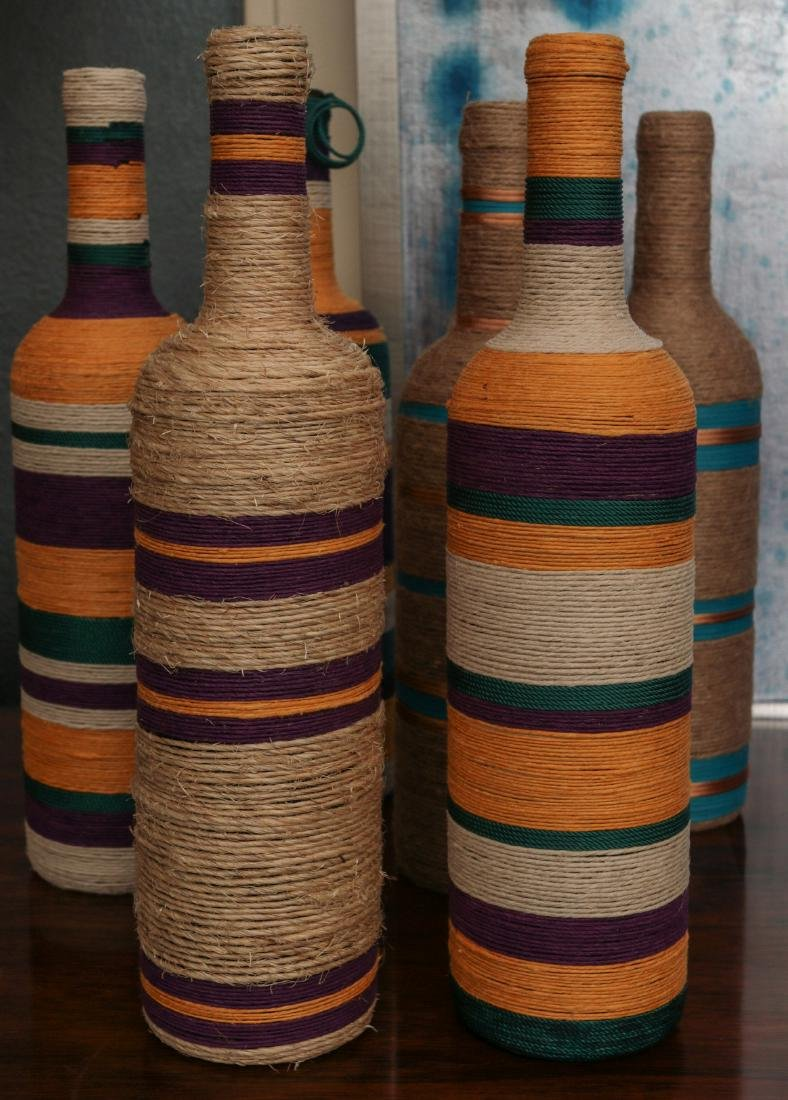 A COLLECTION OF COLORFUL TWINE WRAPPED BOTTLES - 3