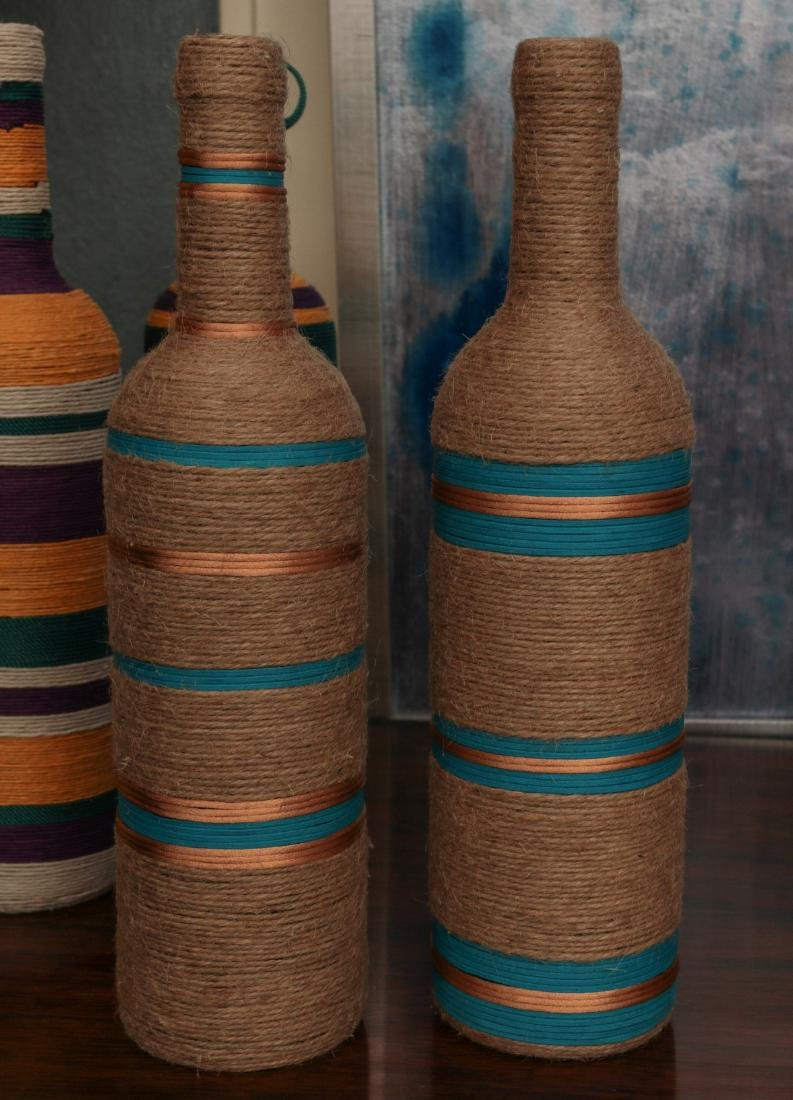 A COLLECTION OF COLORFUL TWINE WRAPPED BOTTLES - 4