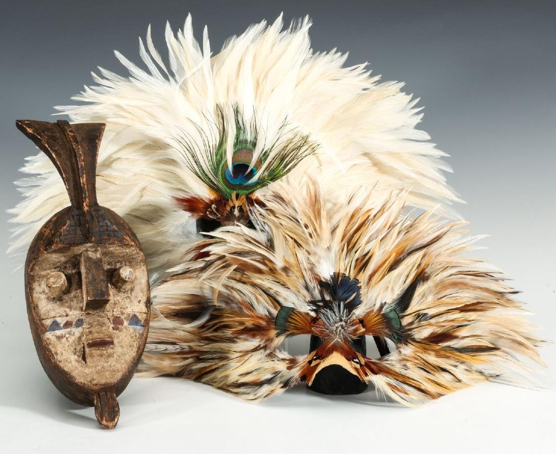 A CARVED WOOD AFRICAN MASK, PLUS FEATHERED MASKS