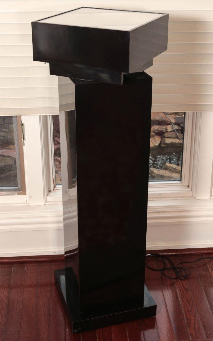 A BLACK ACRYLIC LIGHTED REVOLVING PEDESTAL