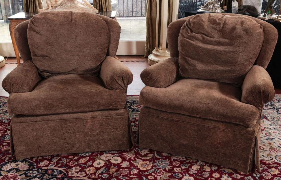 A PAIR OF UPHOLSTERED SWIVEL ARM CHAIRS