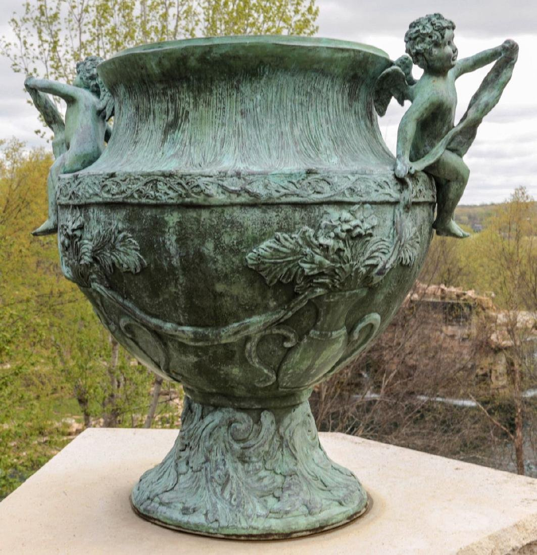 A PAIR 25-INCH BRONZE GARDEN URNS WITH CHERUBS