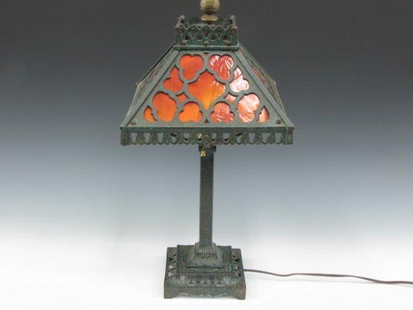 A BOUDOIR SIZE CAST IRON LAMP WITH SLAG GLASS