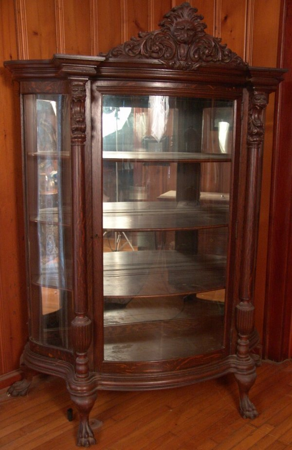 AN AMERICAN OAK CURVED GLASS LION HEAD CHINA CABINET