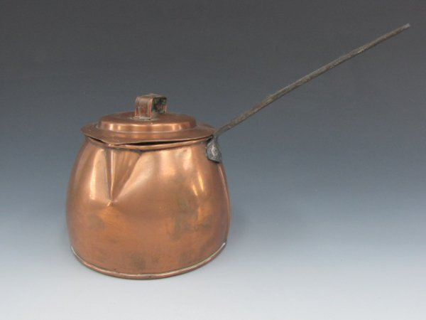 AN EARLY SIDE-POUR COPPER KETTLE WITH IRON HANDLE