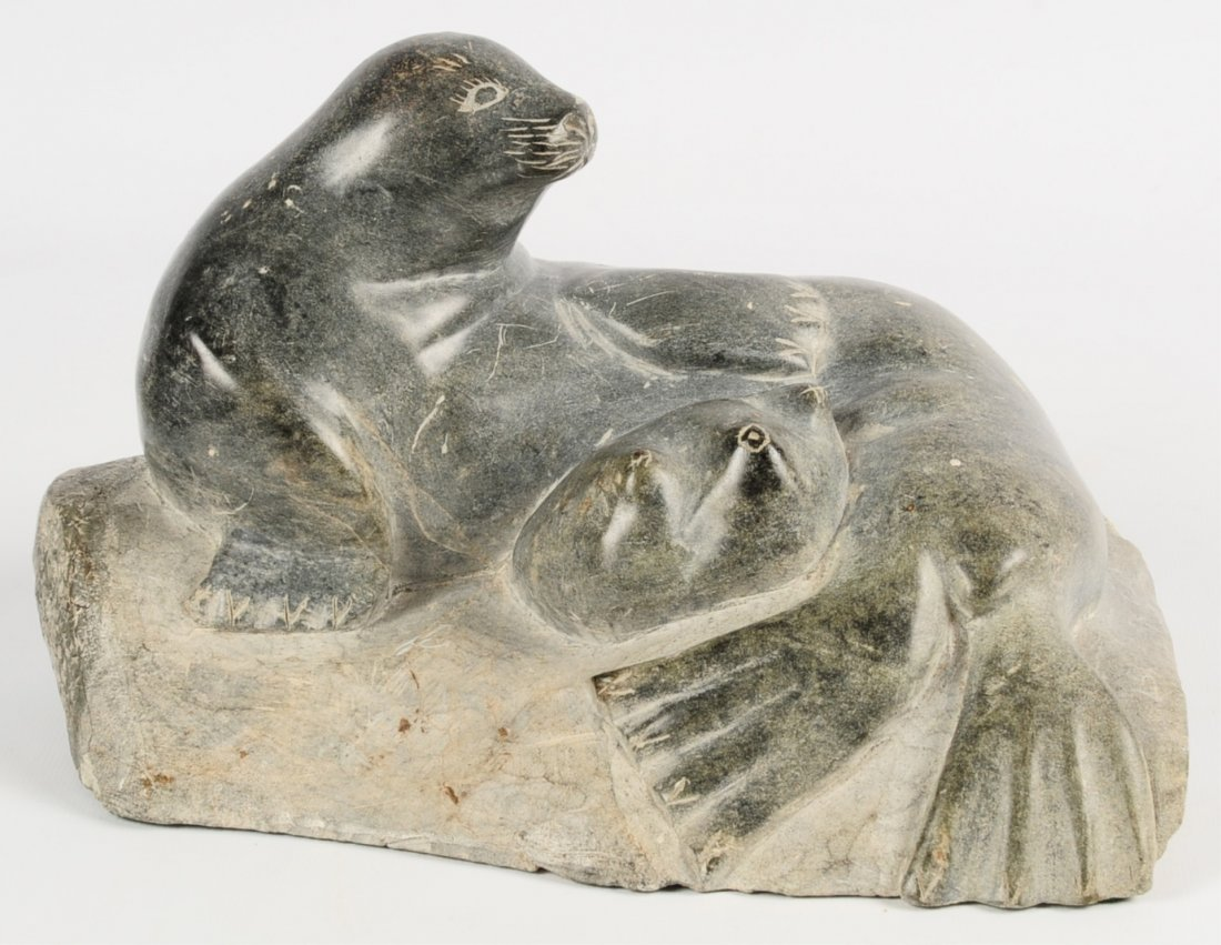 AN INUIT SOAPSTONE SCULPTURE OF SEAL RESTING ON ROCK
