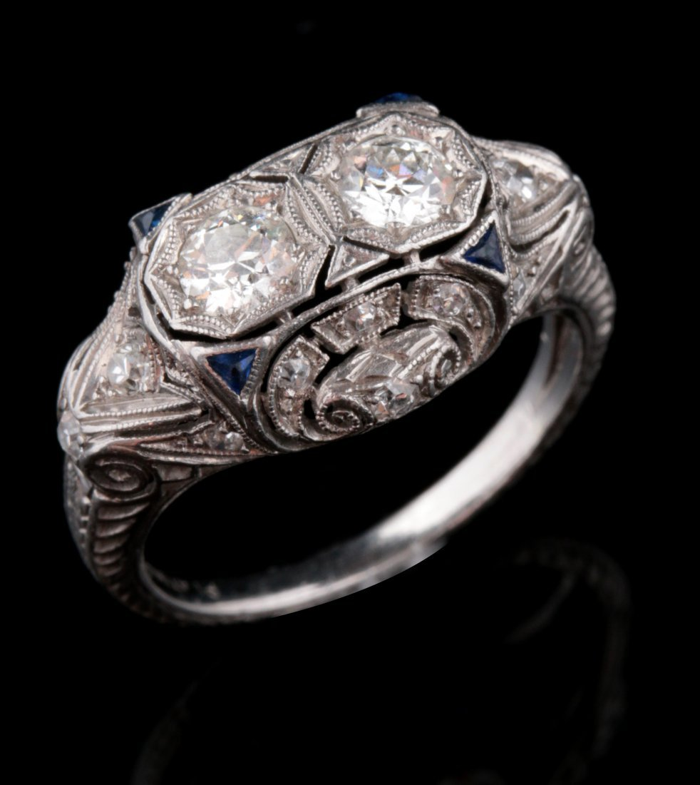 A 1930S PLATINUM DIAMOND AND SAPPHIRE SCROLL RING