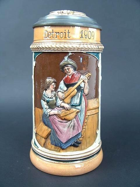 320: 1909 GERMAN POTTERY RELIEF STEIN W/INLAID LID