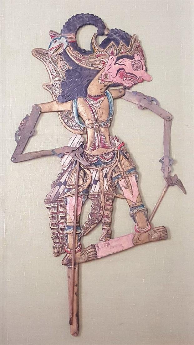 An antique encased Wayang puppet from Java