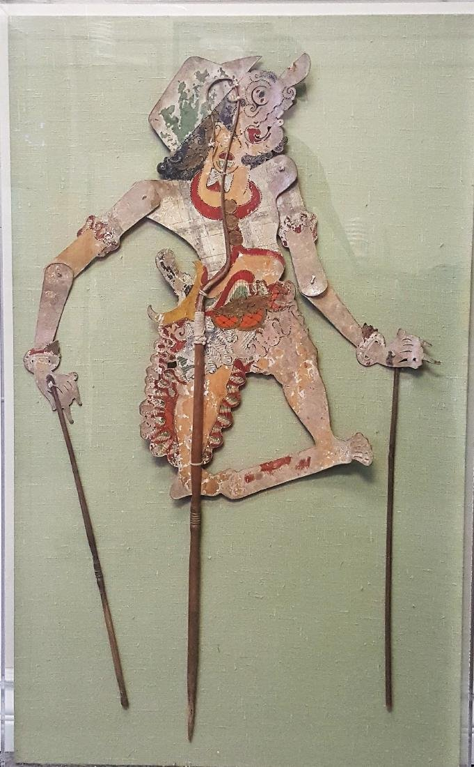 An antique encased Wayang Kulit figure from Java