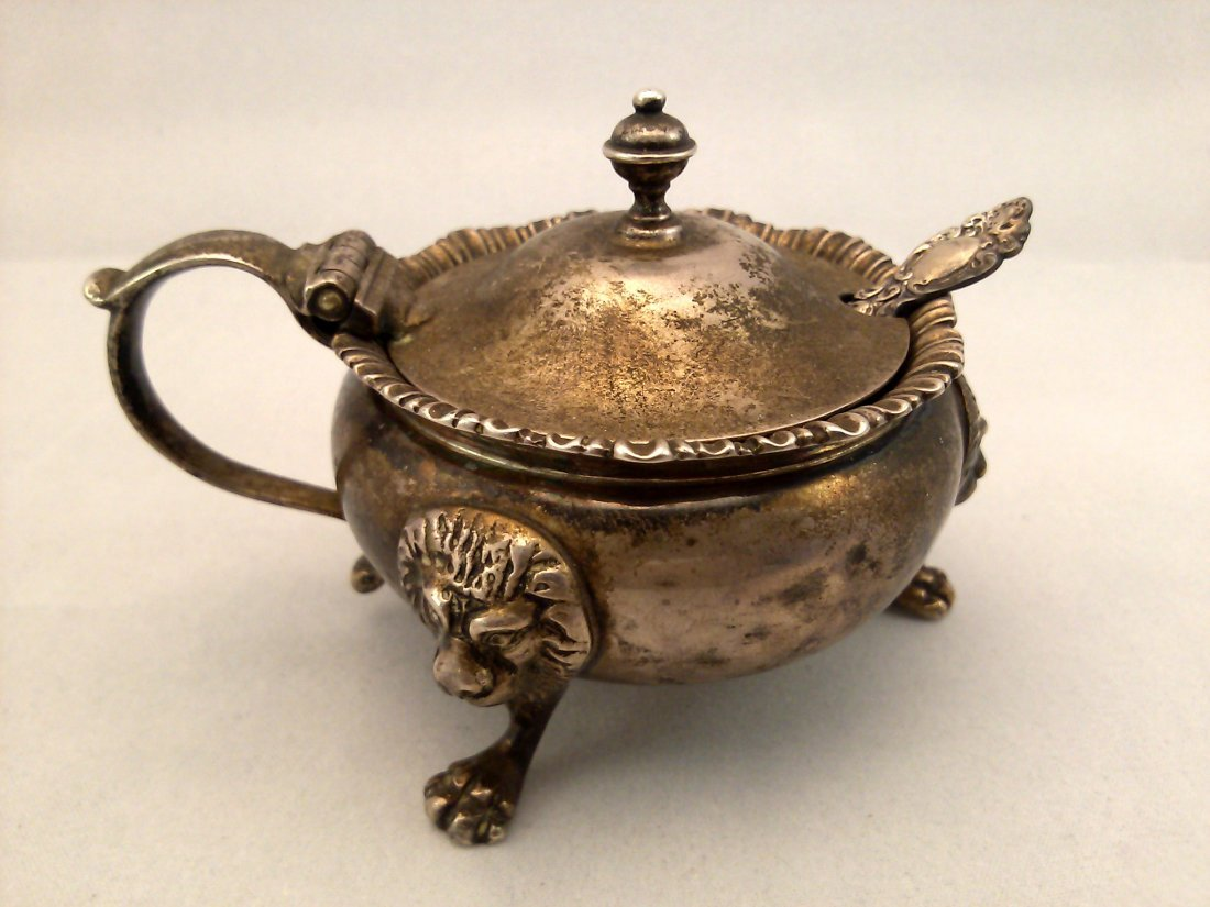 A carved silver mustard cauldron with blue glass liner