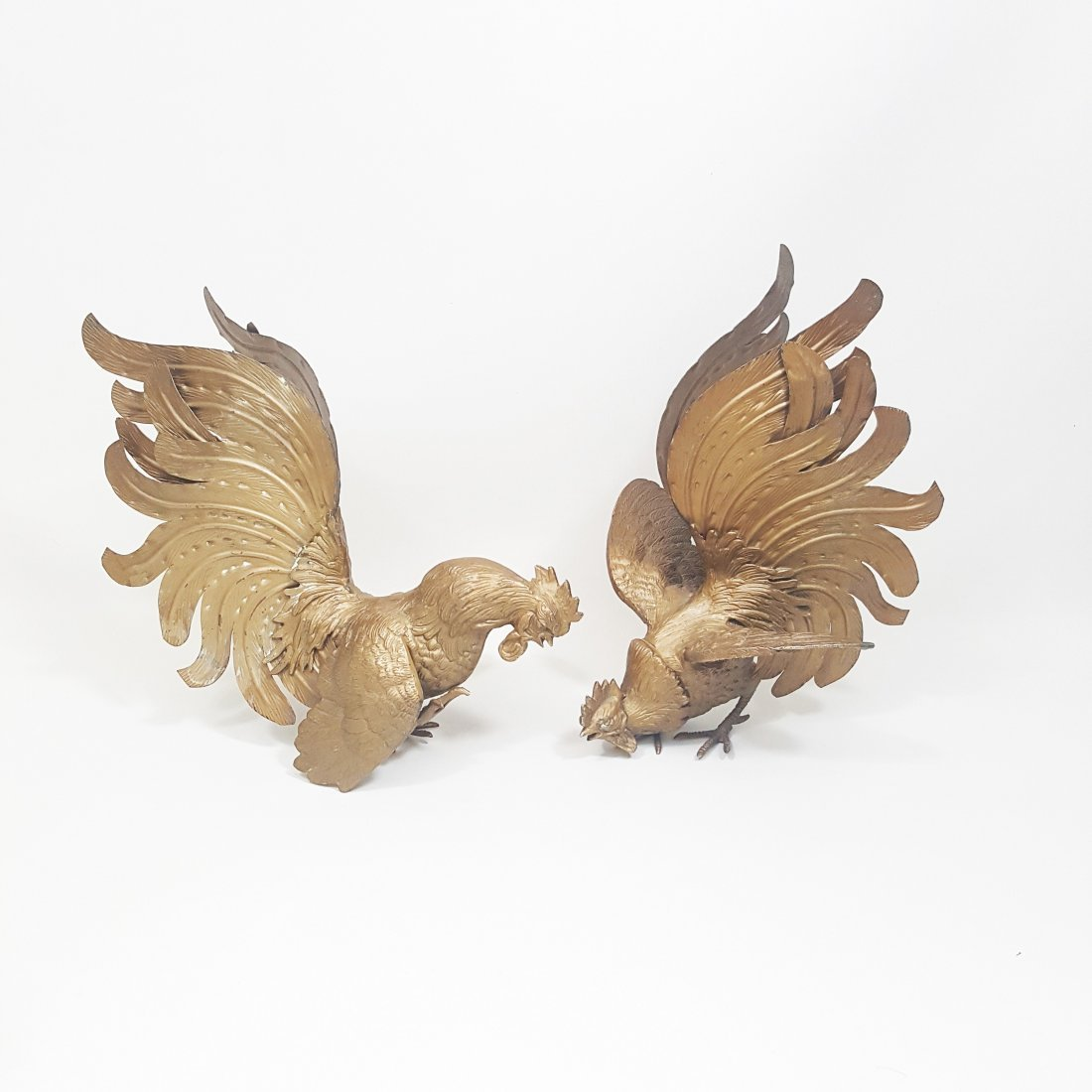 A pair of bronze roosters in fighting position