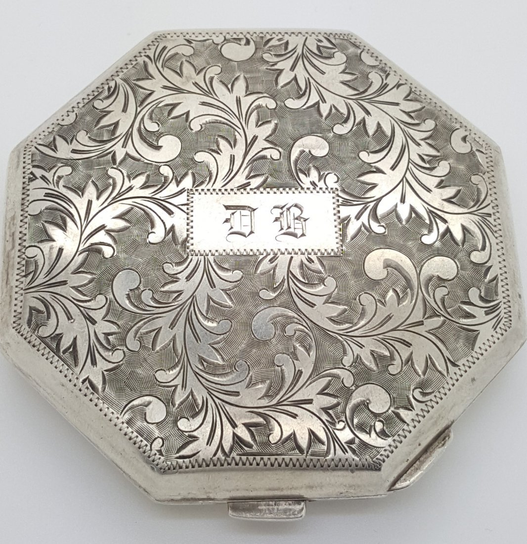 A vintage silver powder box with compartments
