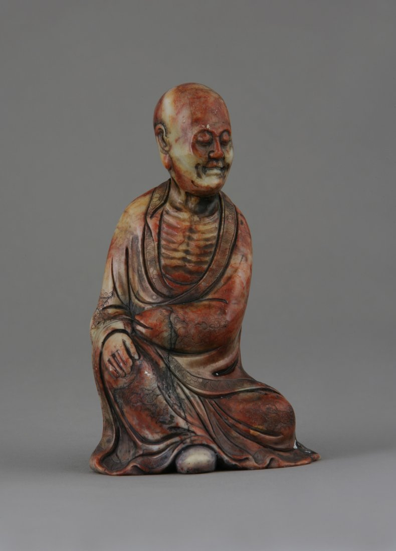 A Chinese Soapstone Figure of a Deity. Red and grey vei
