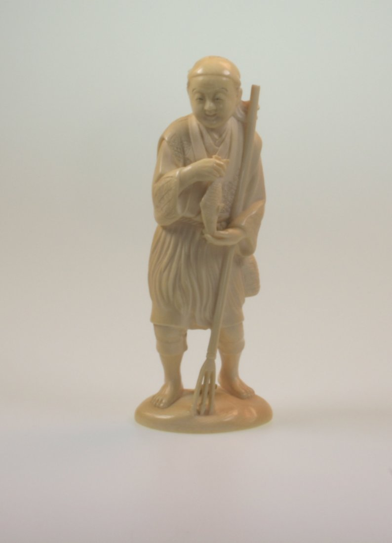A Carved Ivory Figure of a Fisherman with Three Pronged