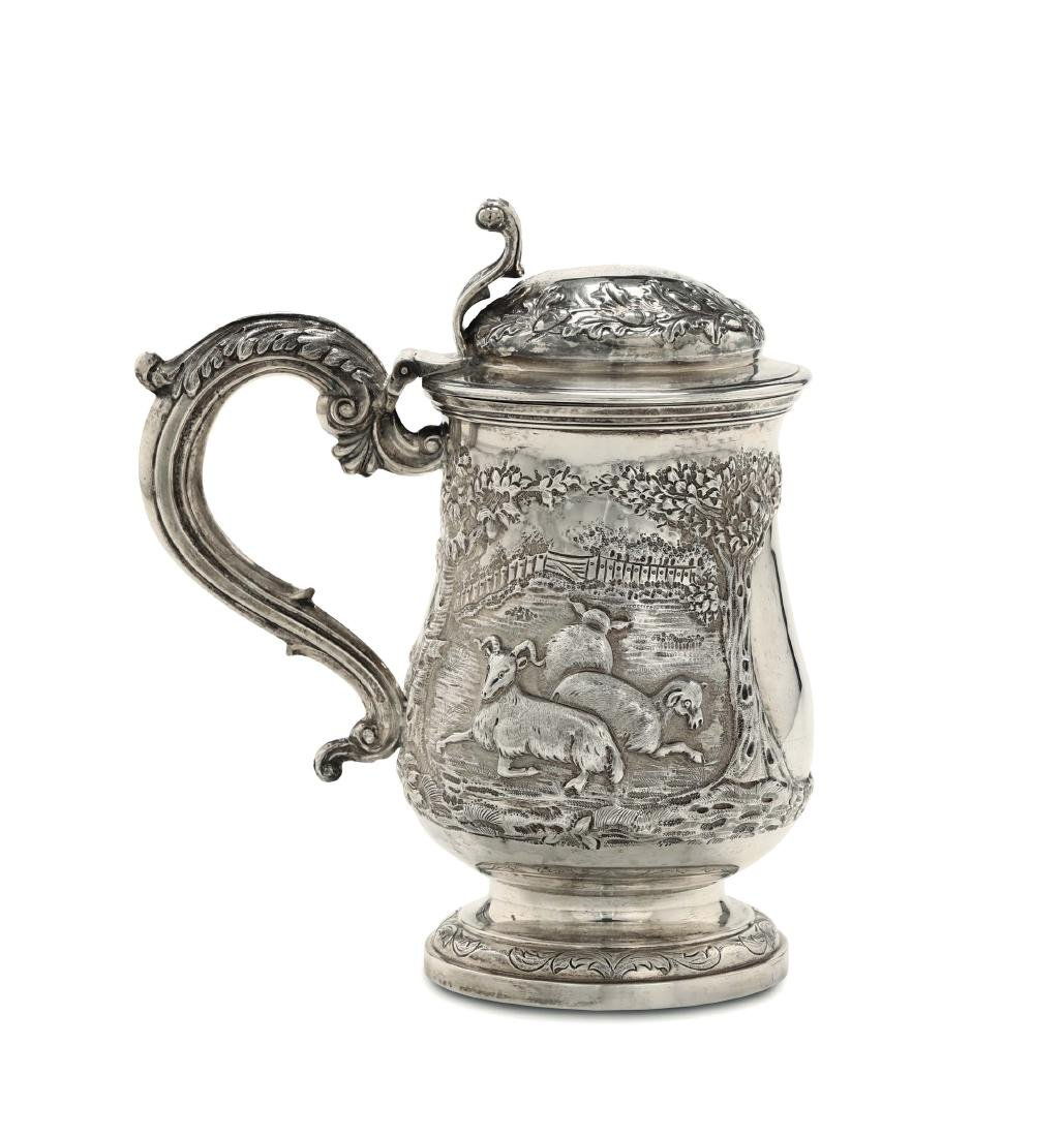 A tankard in Sterling silver, molten, embossed and