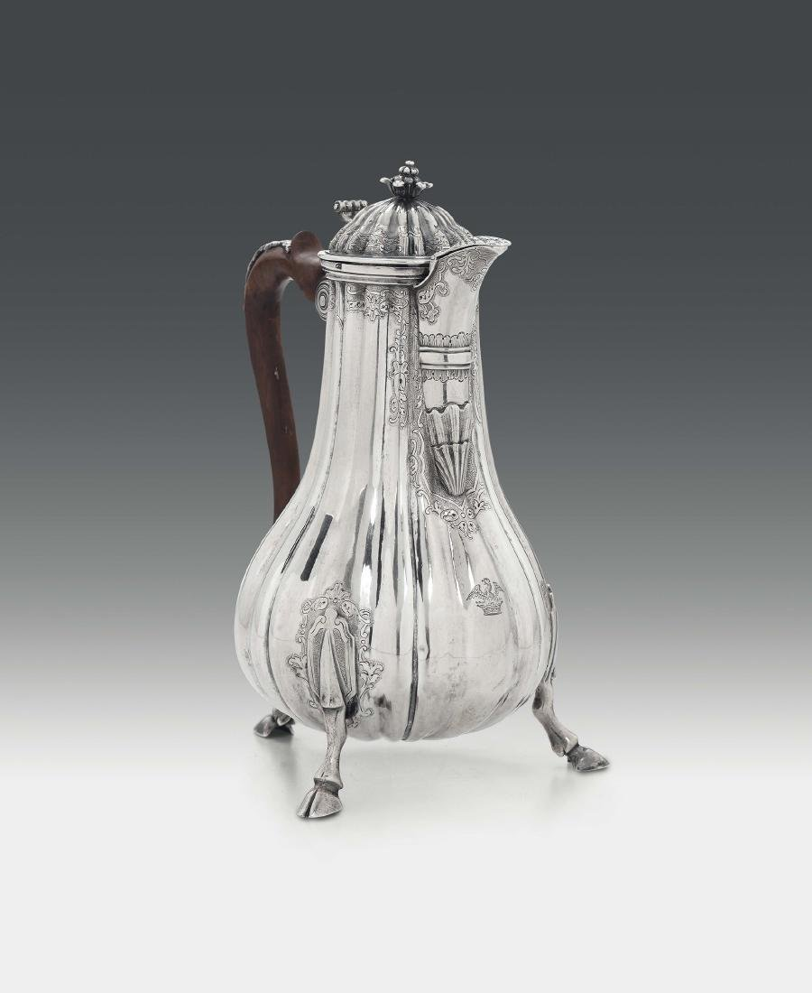 A coffee pot in molten, embossed and chiselled silver,