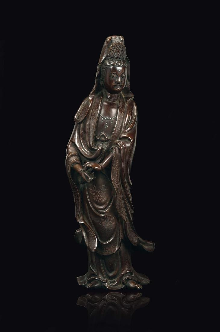 A bronze figure of standing Guanyin with silver inlays
